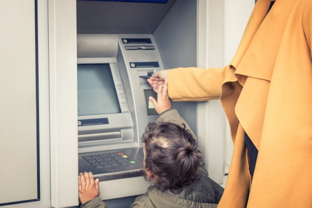 Little girl withdrawing money form ATM with help of mother.